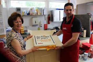 RRT presenting a celebratory cake to the Friary General Manager