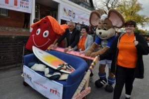 """SAFE housing mascot (left), Deputy Police Crime Commissioner, Hardyal Dhindsa (second from left), SAFE Service Manager & Consortia Lead, Sue Wood (Centre), with Chesterfield FC """"Chester the Mouse"""" and Megan (a community member representing those the event was supporting) pushing the Sofa Surf."""